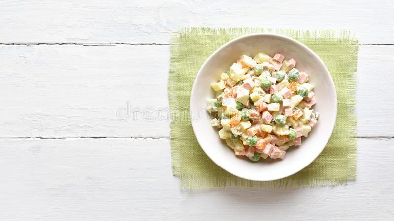 Russian salad \'Olivier. Traditional russian salad \'Olivier\' from boiled vegetables and sausage with mayonnaise in bowl. Russian New Year or Christmas salad on royalty free stock photography