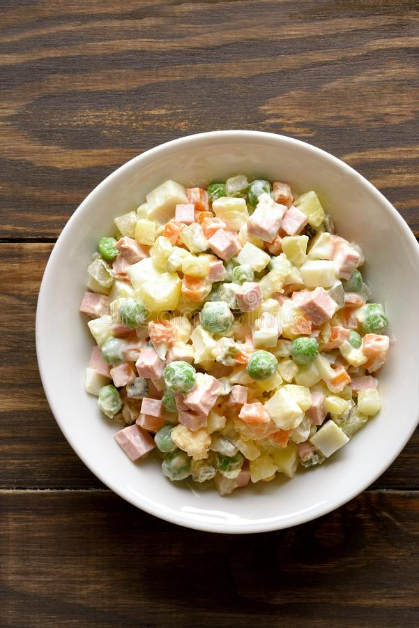 Russian salad \'Olivier. Traditional russian salad \'Olivier\' from boiled vegetables and sausage with mayonnaise in bowl. Russian New Year or Christmas salad on stock photography