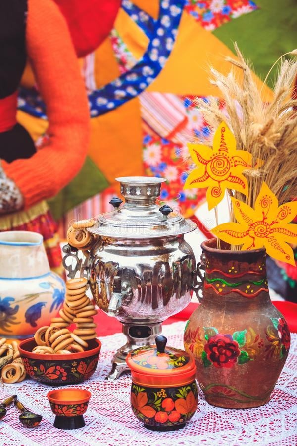 Russian samovar with bagels at the festival of Shrovetide. Samovar with bagels crock and other Russian wooden utensils on the table stock photography