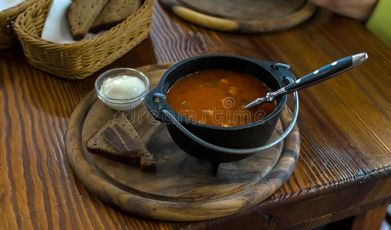 Russian soup, borscht, in a cast iron pot on the background of a womans hand. On a wooden table in a stylish restaurant, in the old Russian style royalty free stock image