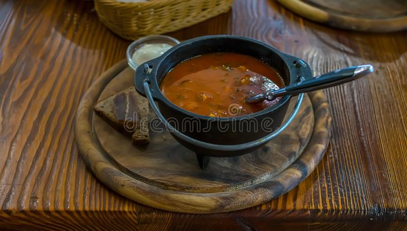 Russian soup, borscht, in a cast iron pot on the background of a womans hand. On a wooden table in a stylish restaurant, in the old Russian style stock photography