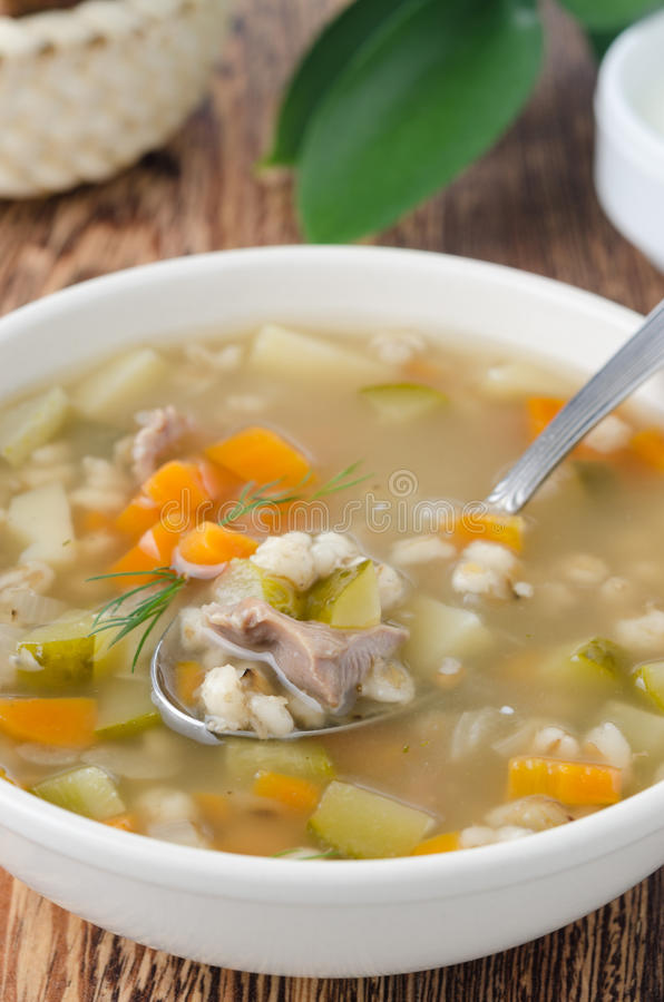 Russian soup rassolnik in a white bowl, spoon of soup closeup. Russian soup rassolnik in a white bowl on the table, spoon of soup closeup royalty free stock images
