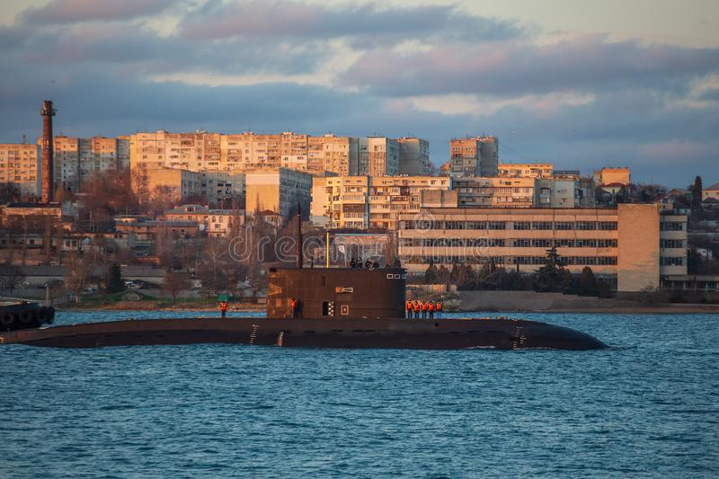 Russian submarine in city harbour with residential buildings at background. Sea NAVY boat royalty free stock photo