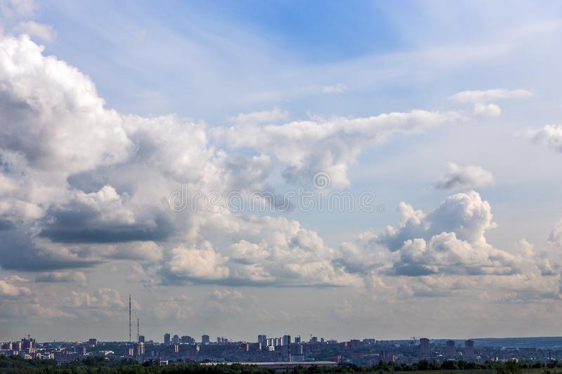 Russian summer daylight cityscape with large cumulus clouds and tiny horizon line of the panel condominium houses royalty free stock photography
