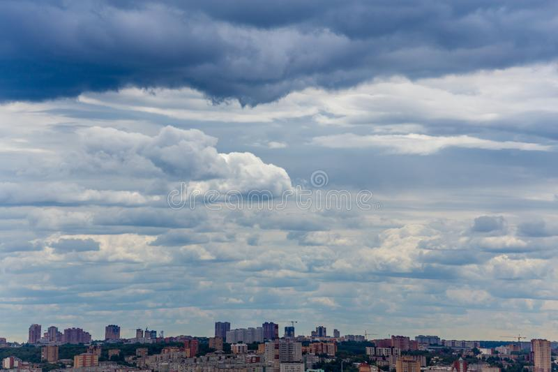 Russian summer daylight cityscape with large cumulus clouds and tiny horizon line of the panel condominium houses.  stock image