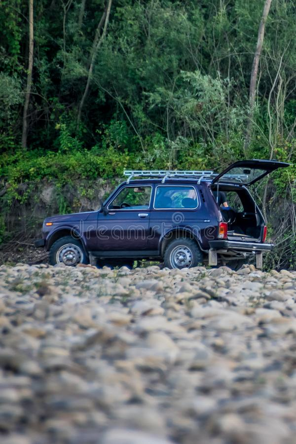 Russian SUV Lada Niva 4x4 on the riverside. Compact SUV camping on the nature. Famous russian folk four wheel drive car Lada Niva 4x4 or VAZ-2121. Serial royalty free stock photo