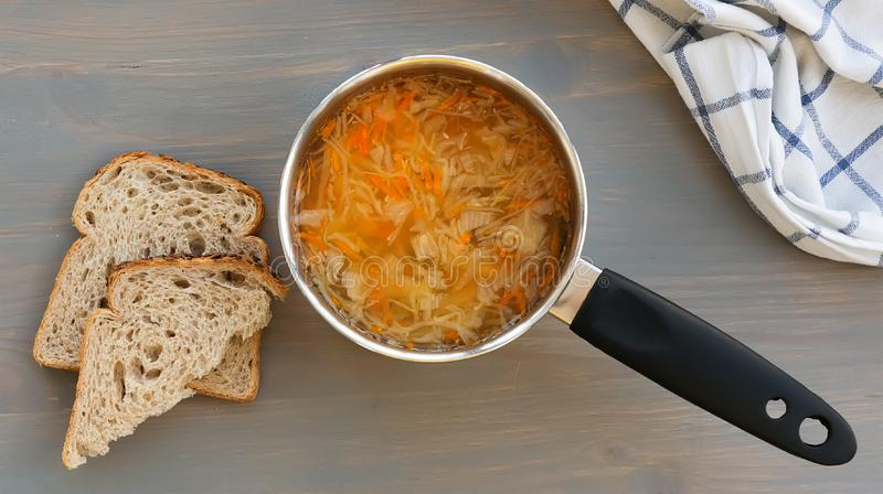 Russian traditional food. Vegetable soup shchi in a ladle and bread on a gray background. Top view royalty free stock image