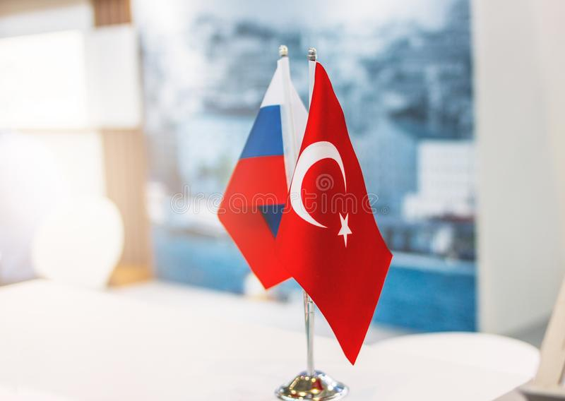 Russian and Turkish flags on metal stand on business conference or exhibition, international relations, trade, cooperation concept. Russian and Turkish flags on stock image
