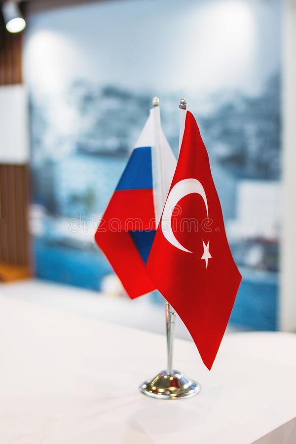 Russian and Turkish flags on metal stand on business conference or exhibition, international relations, trade, cooperation concept. Russian and Turkish flags on royalty free stock photos