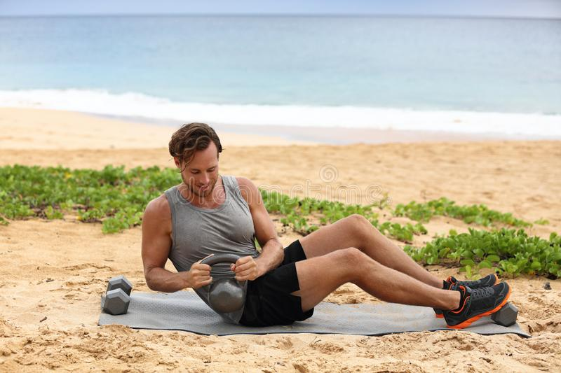 Russian Twist - Fitness man exercising on beach training with kettlebells working out core, obliques and abdominal muscles. Male. Fitness instructor doing abs royalty free stock image