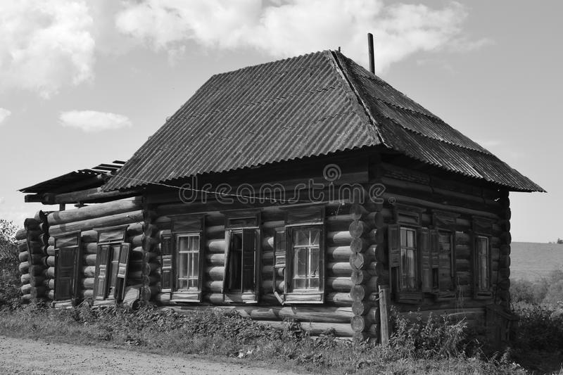 Russian village - house with shutters. Russian village - an old house with wooden shutters by the road, without electricity, with a canopy, black and white photo stock photos