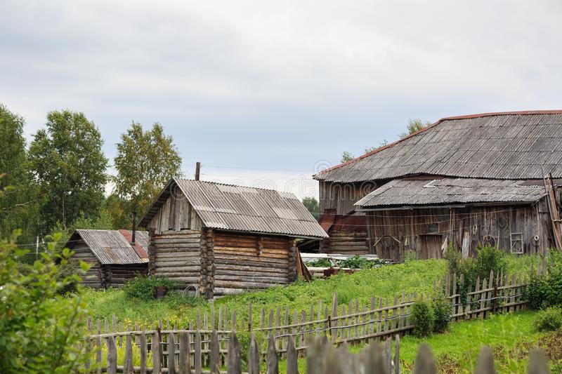 Russian village in summer. Country yard with old log houses. Surrounded with a rickety wooden fence. Village of Visim, Sverdlovsk region, Russia royalty free stock images