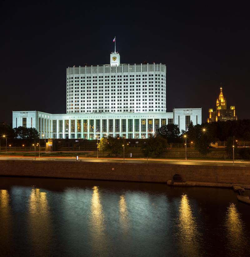 Russian White House House of the Government of the Russian Federation with famouse Stalin skyscaper on the background. In Moscow at night. Colorful illumination royalty free stock image