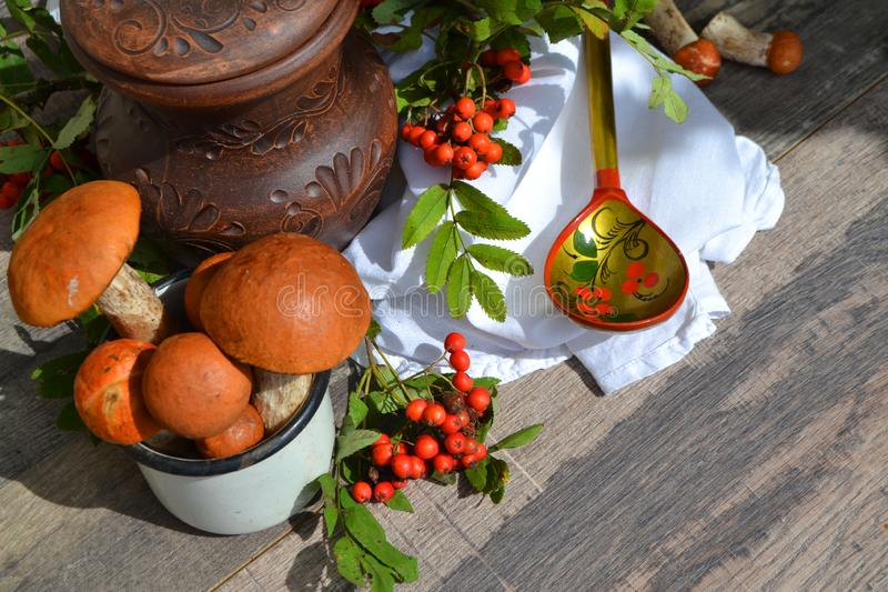 Delicious russian wild mushrooms from forest, with red caps. Ceramic jug and spoon khokhloma on rustic wooden table and rowan stock photo