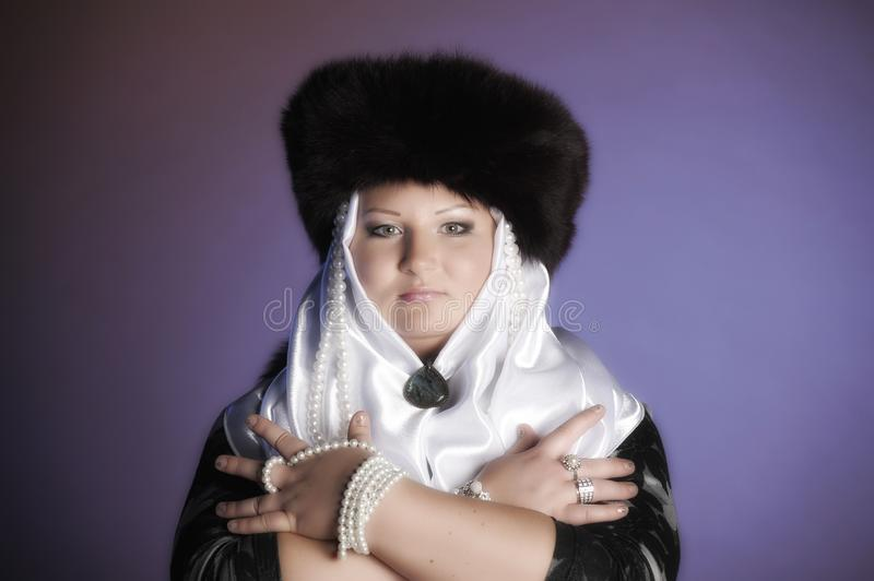 Russian woman in a fur hat, white scarf and with pearls royalty free stock photography