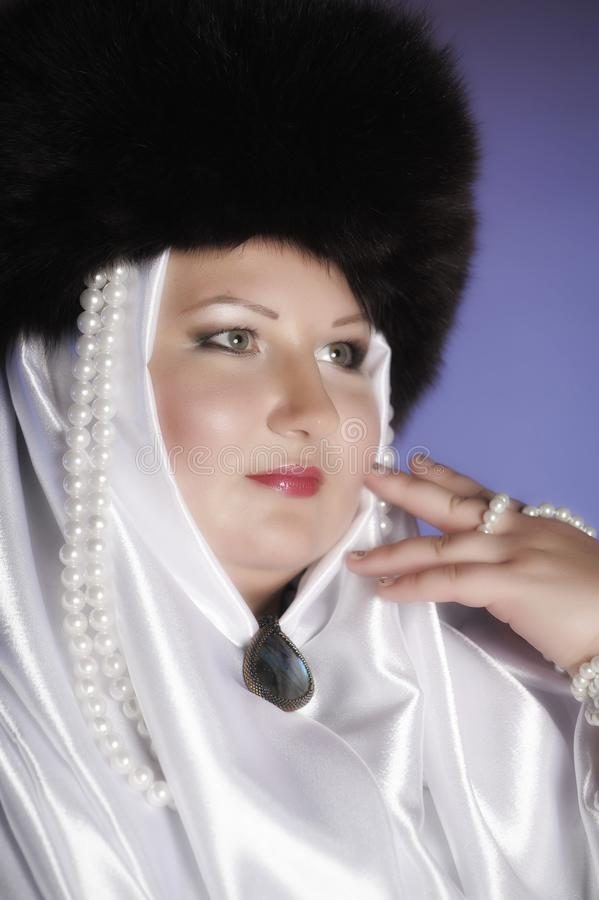 Russian woman in a fur hat, white scarf and with pearls. Historical portrait stock image