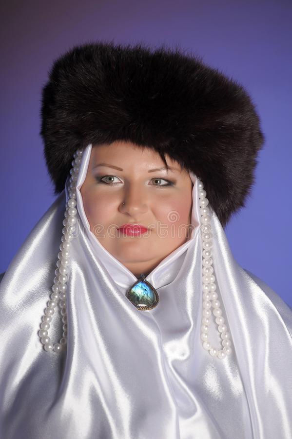 Russian woman in a fur hat, white scarf and with pearls. Historical portrait royalty free stock photo