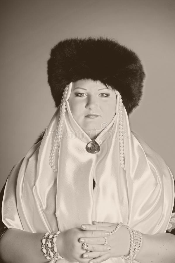 Russian woman in a fur hat, white scarf and with pearls. Historical portrait stock photos