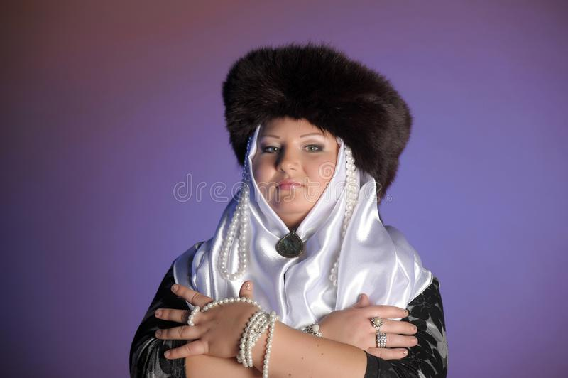 Russian woman in a fur hat, white scarf and with pearls. Historical portrait stock photo