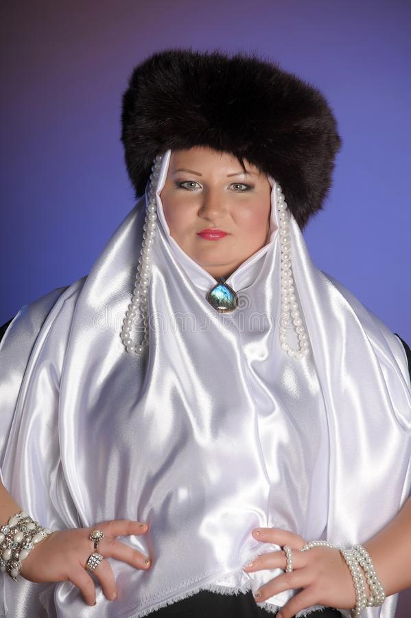 Russian woman in a fur hat, white scarf and with pearls. Historical portrait royalty free stock image