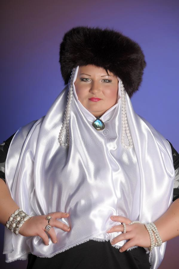 Russian woman in a fur hat, white scarf and with pearls. Historical portrait stock images