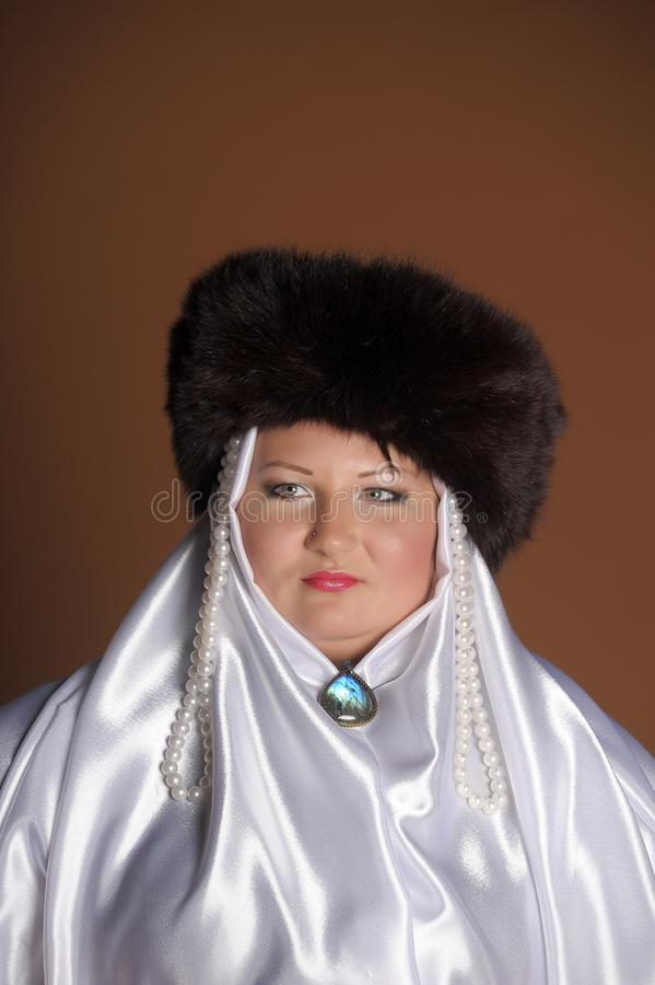 Russian woman in a fur hat, white scarf and with pearls. Historical portrait royalty free stock photography