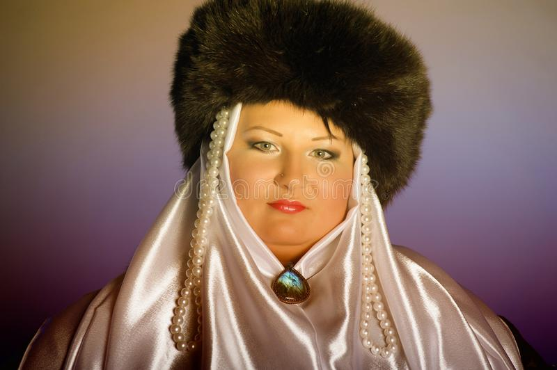 Russian woman in a fur hat, white scarf and with pearls. Historical portrait stock photography