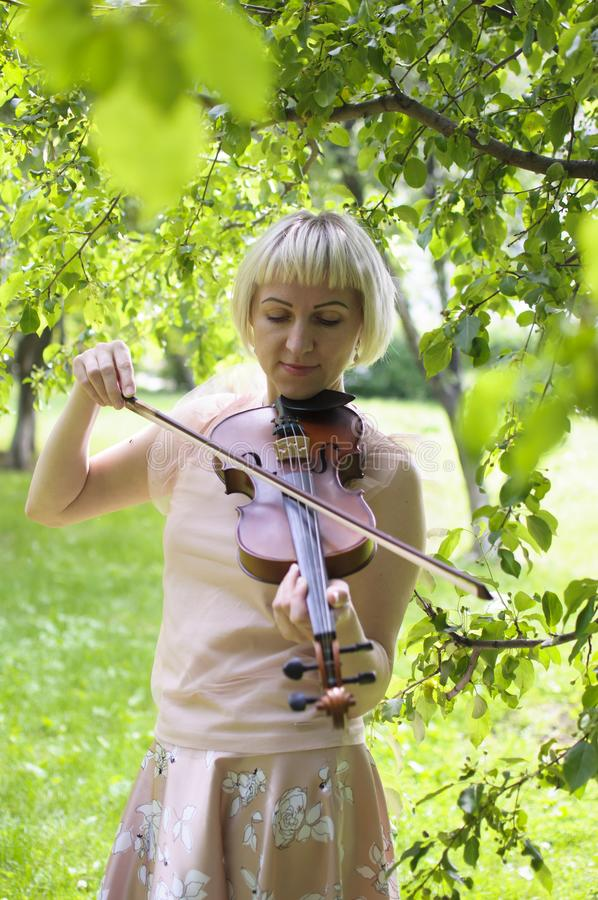 The Russian woman plays a violin in the park in the summer stock photo