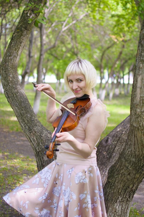 The Russian woman plays a violin in the park in the summer royalty free stock photos