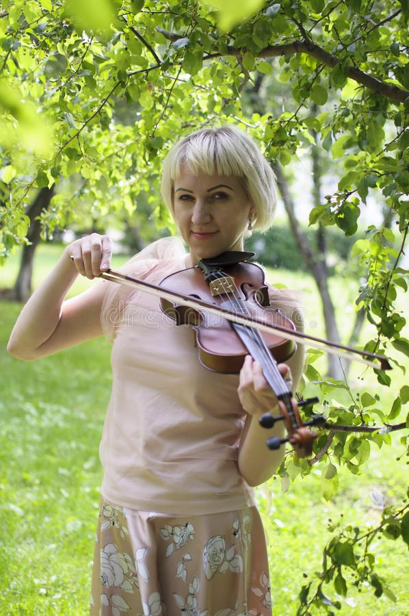 The Russian woman plays a violin in the park in the summer royalty free stock photo
