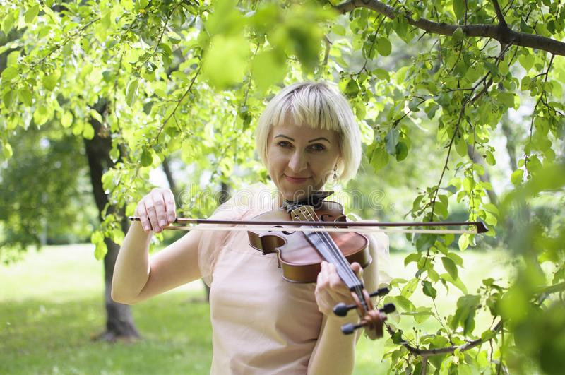 The Russian woman plays a violin in the park in the summer stock image