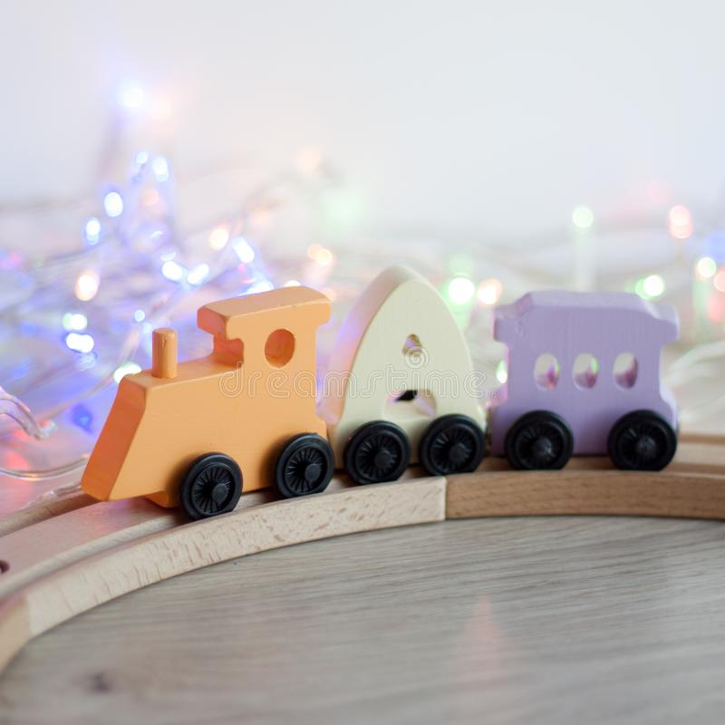 Russian wooden letters train alphabet with locomotive on wood railway. Light shades colors, black wheels. Early childhood educatio. N, learning to read royalty free stock photo