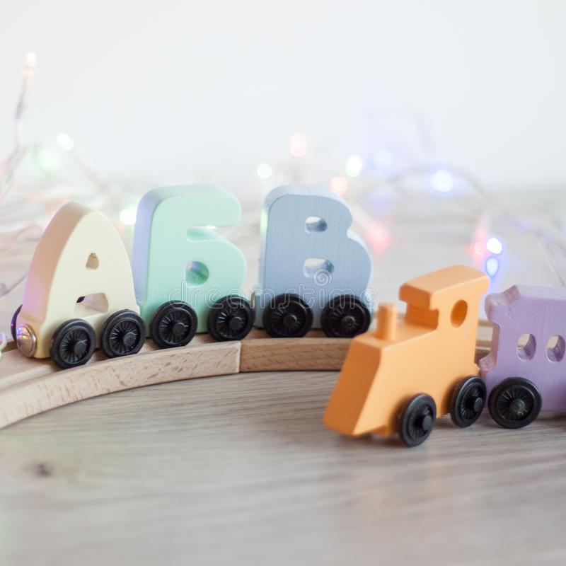 Russian wooden letters train alphabet with locomotive on wood railway. Light shades colors, black wheels. Early childhood educatio. N, learning to read stock images