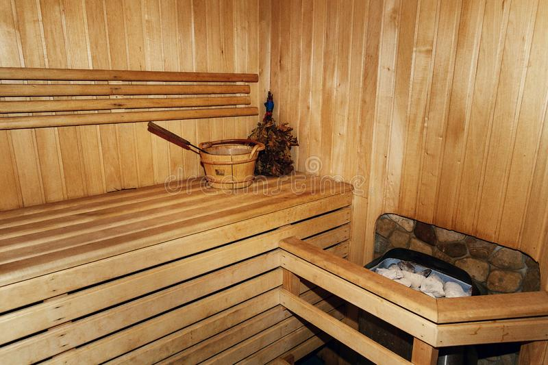 Russian wooden sauna room, lumber rustic bench in bath house, wooden bucket with water and birch leaf broom, healthy leisure royalty free stock image