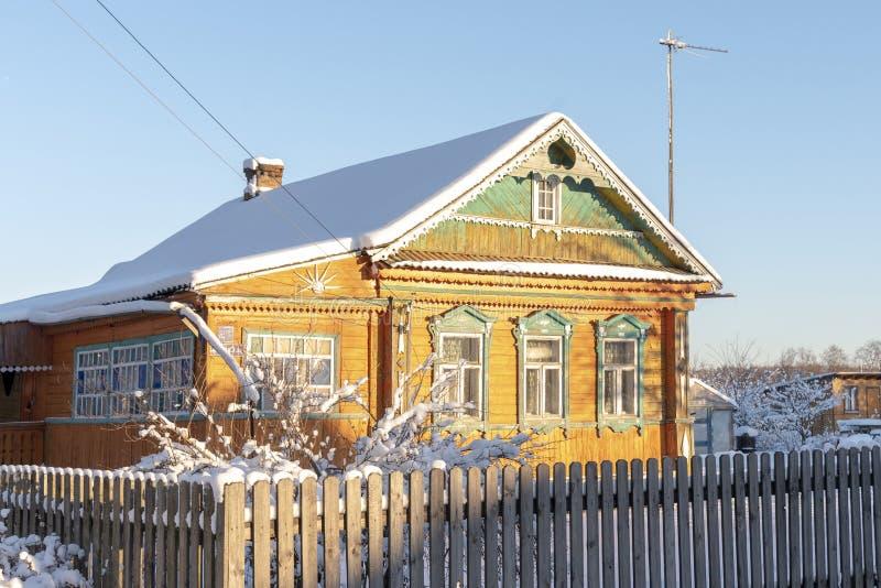 RussiaOld lantligt trähus i ryssby i solig dag för vinter Moskow region, Ryssland royaltyfri fotografi