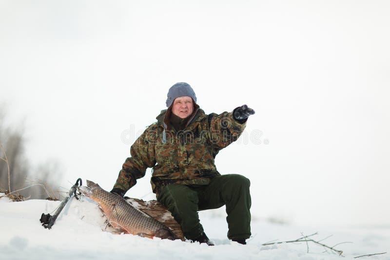 Russin Spearfishing con el speargun tiró un pescado grande debajo del hielo imagenes de archivo
