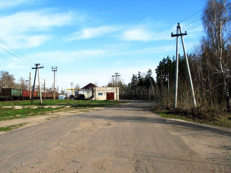 Russisch landelijk landschap met de lege natte weg van het plattelandsvuil stock afbeelding