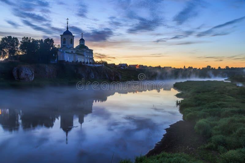 Russisch orthodox klooster Mist over de rivier dichtbij de klip en de kerk Ural, Chusovaya stock afbeelding