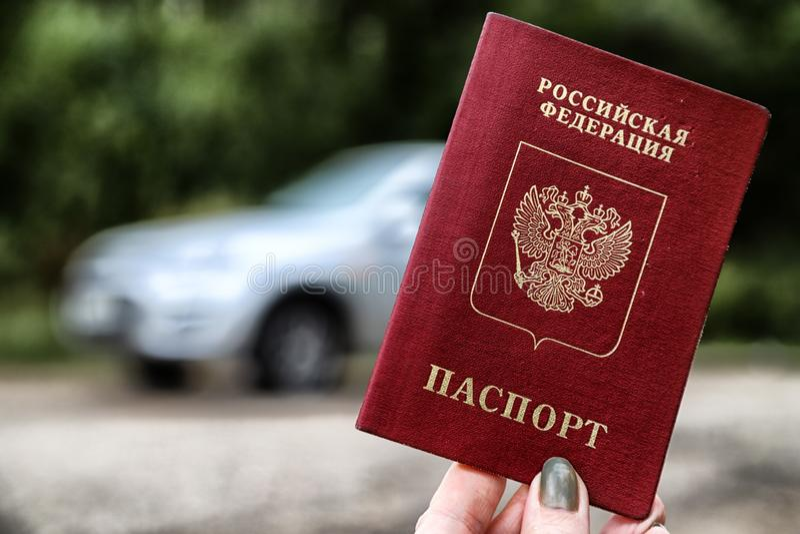 Russisch paspoort in de hand van vrouw en autoachtergrond royalty-vrije stock afbeeldingen
