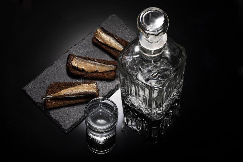 Russisch voedsel Snack met sprot en brood Karaf met alcohol en glas met wodka stock fotografie