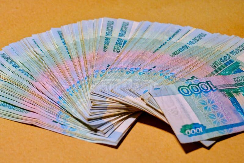 Russische Banknoten 1000 Rubel werden heraus als Fan auf einem Kraftpapier verbreitet stockfotografie