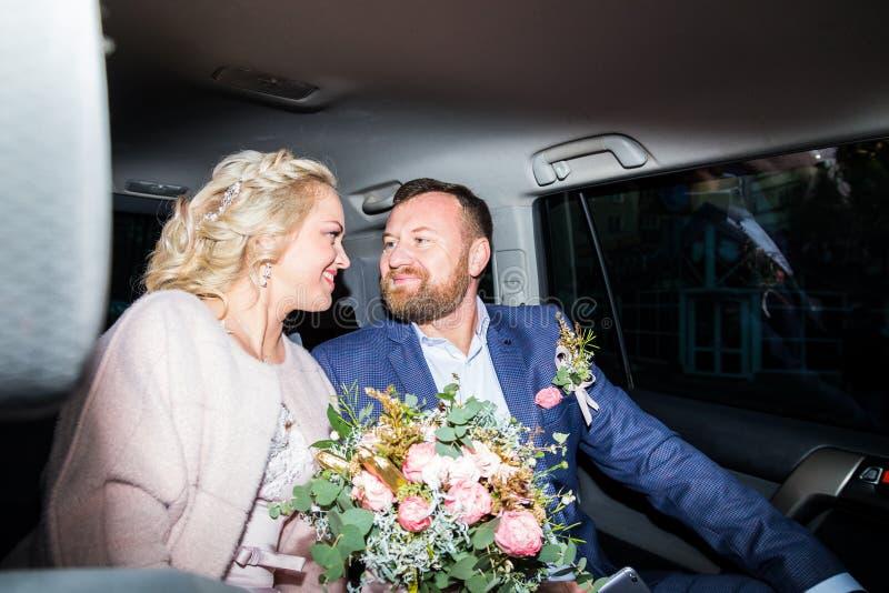 Russische Braut und Br?utigam im Auto lizenzfreie stockfotografie