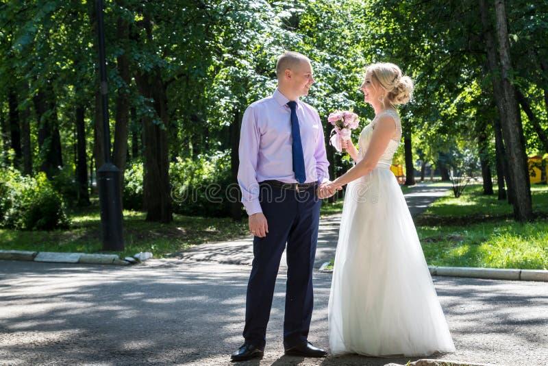 Russische Braut und im grünen Stadtpark zusammen sich pflegen lizenzfreie stockfotografie
