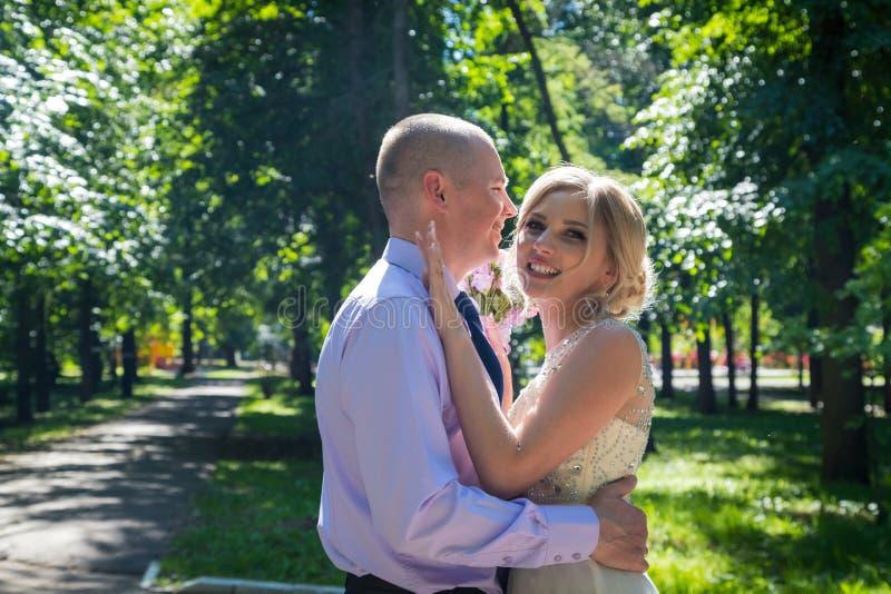 Russische Braut und im grünen Stadtpark zusammen sich pflegen lizenzfreie stockbilder