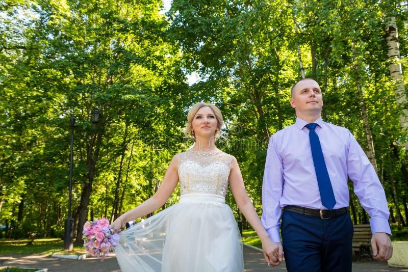 Russische Braut und im grünen Stadtpark zusammen sich pflegen lizenzfreies stockbild