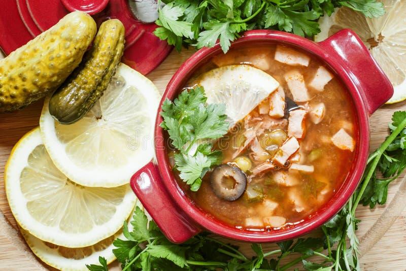 Russische Fleischsolyanka-Suppe in keramischen eingeteilten roten Töpfen, Spitzenv stockbilder