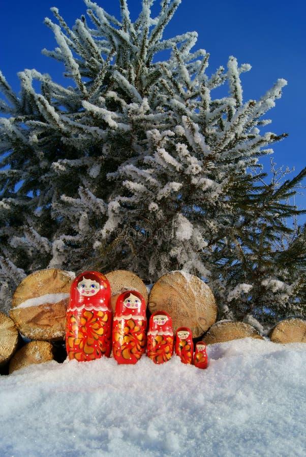 Russische hölzerne Puppen auf dem Schnee stockfotos