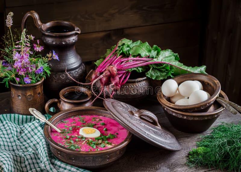 Russische kalte Suppe mit Rote-Bete-Wurzeln, Schüsseln, Löffel, Krug, Grün auf dunklem Holztisch lizenzfreie stockfotos