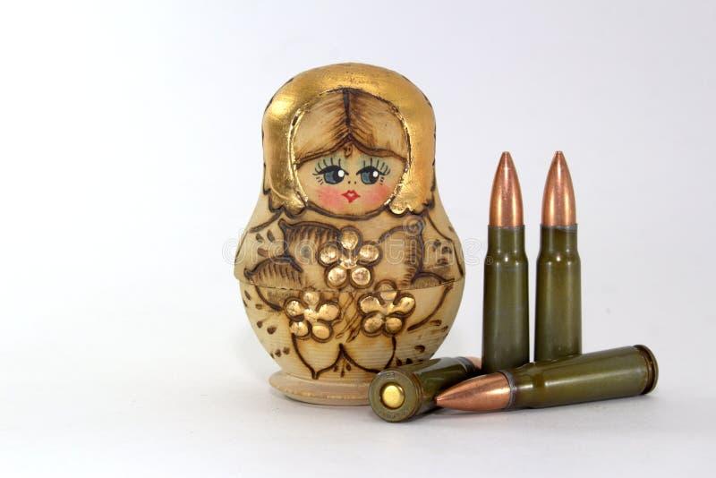 Russische matryoshka en verscheidene patronen voor de geweren van de Kalashnikovaanval stock foto