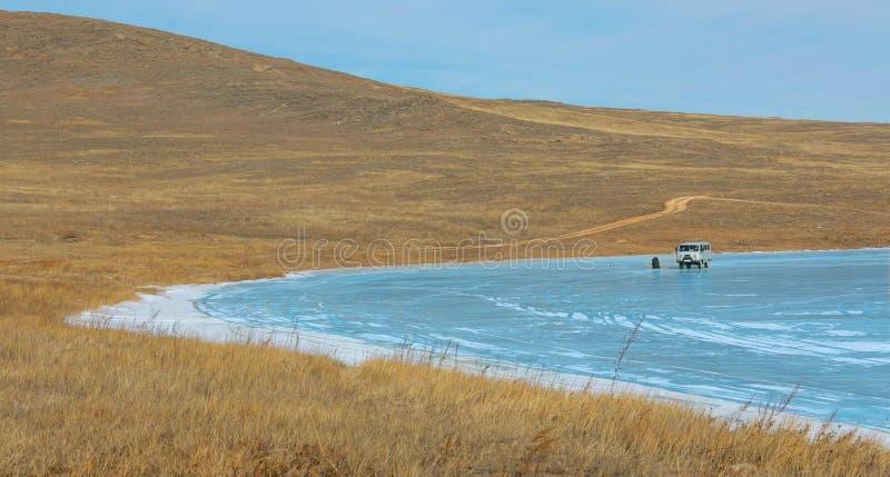 Russische militaire jeep voor de reis van de de winterreis en een toerist op het ijsoppervlakte van meerbaikal stock fotografie
